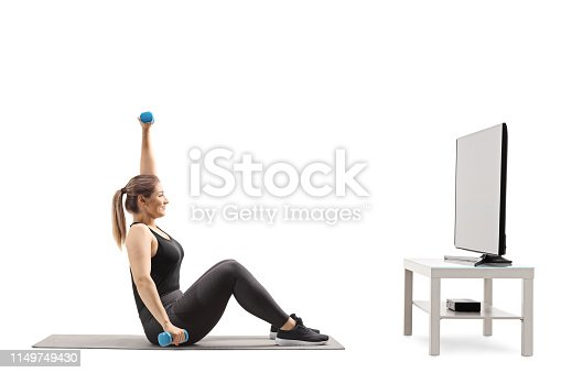 istock Young woman exercising infront of a TV 1149749430