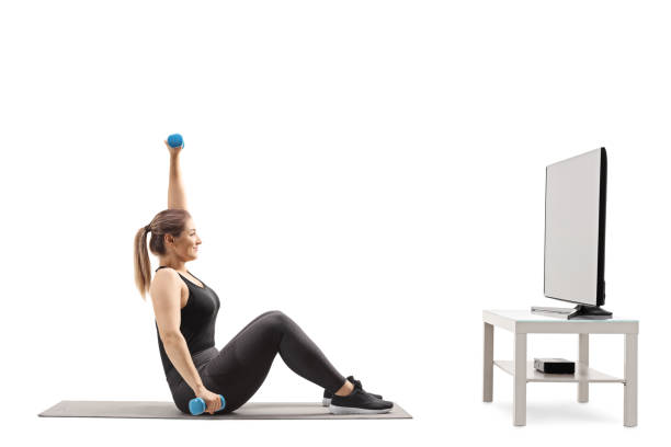 Young woman exercising infront of a TV stock photo