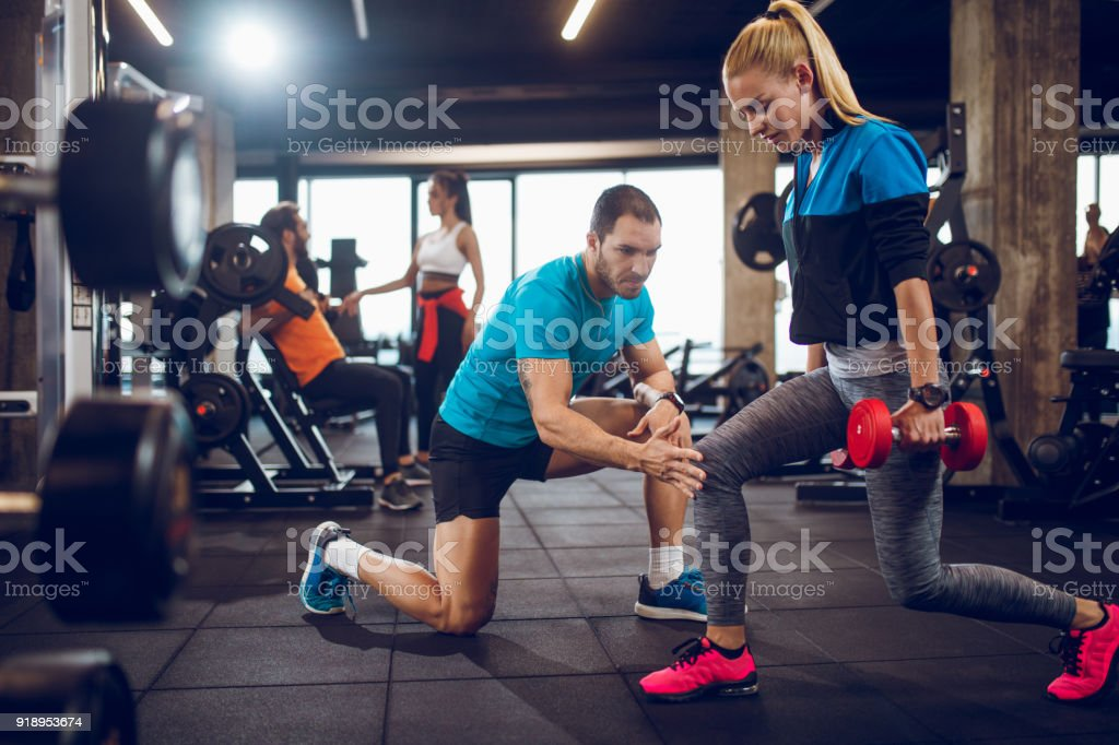 Young woman exercising lunges with dumbbells at the gym stock photo
