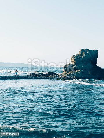 istock Young woman exercising on a pier in the sea 598054960