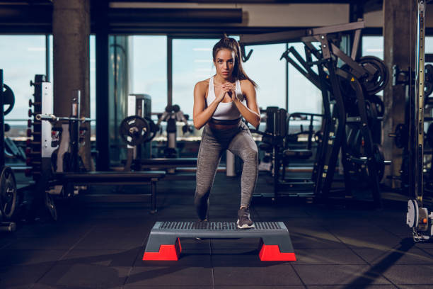 Young woman exercising on step aerobics equipment at gym stock photo