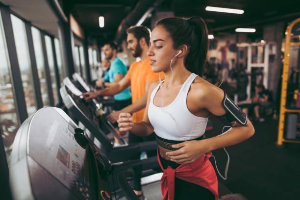 young woman exercising on treadmill - palestre foto e immagini stock