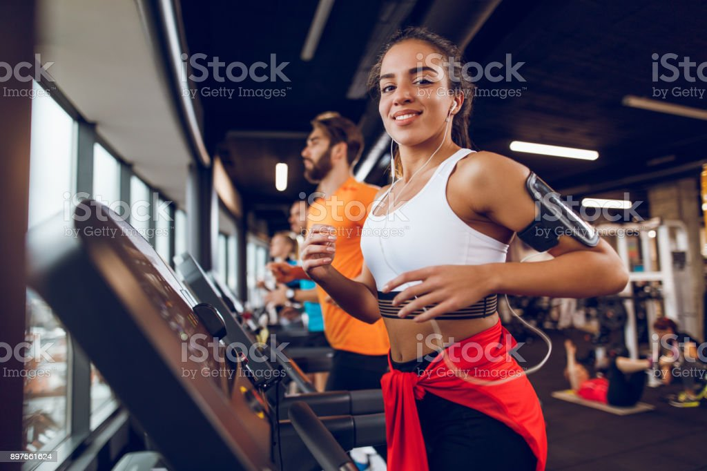 Young woman exercising on treadmill stock photo