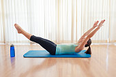 Young woman exercising. (V-ups exercise) Abs core workout.