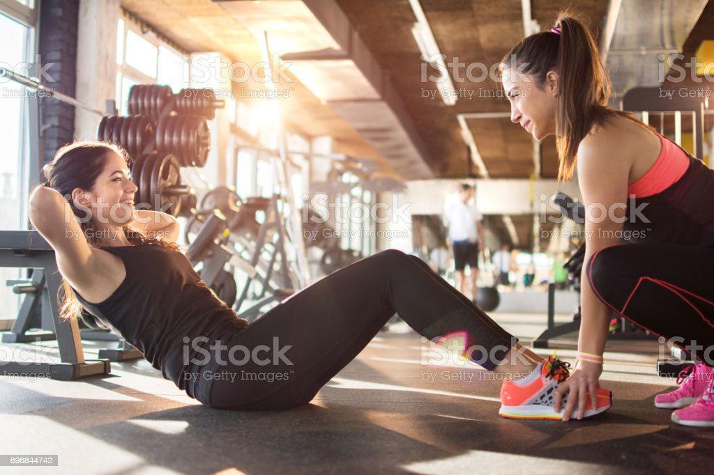 Young woman exercising sit-ups with assistance of female friend in gym. - foto stock