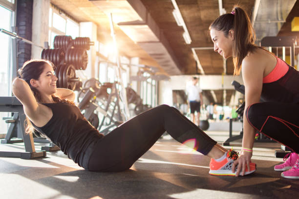 Young woman exercising sit-ups with assistance of female friend in gym. stock photo