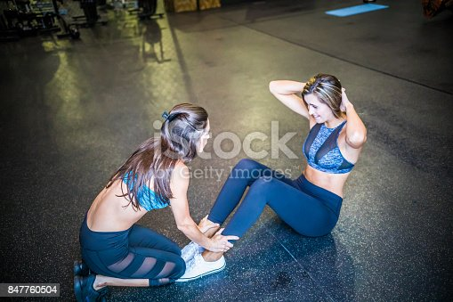 istock Young woman exercising sit-ups with assistance of female friend in gym. 847760504