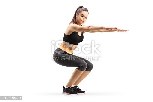 istock Young woman exercising squats 1147186024