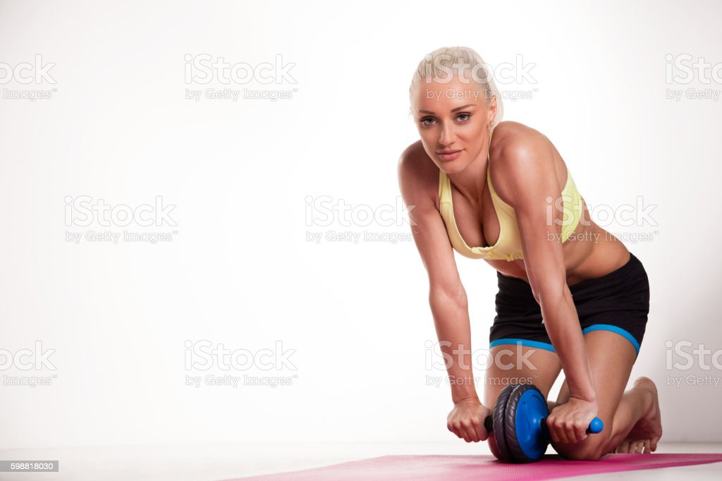 Young woman exercising with abdominal toning wheel on the white stock photo
