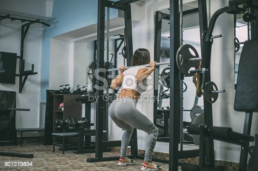 670937518istockphoto Young woman exercising with barbell 927273834