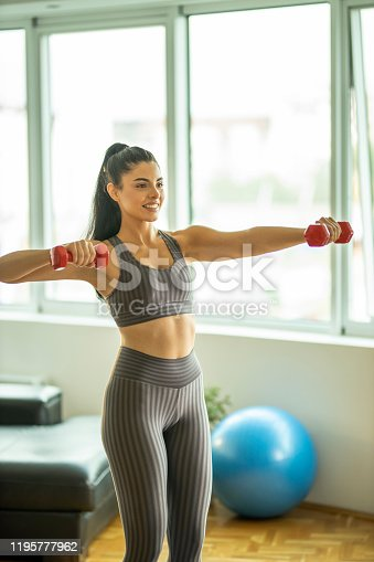 1035512048istockphoto Young woman exercising with dumbbells at home in a living room 1195777962