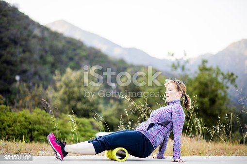 A young woman uses a foam roller during her workout