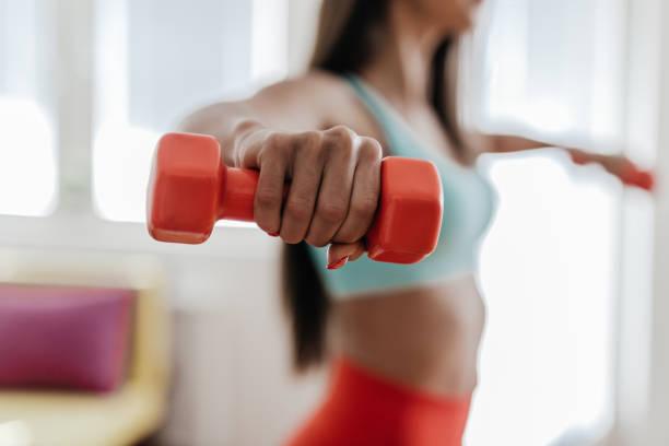 Jovem mulher exercitando com seus pesos na sala de estar - foto de acervo