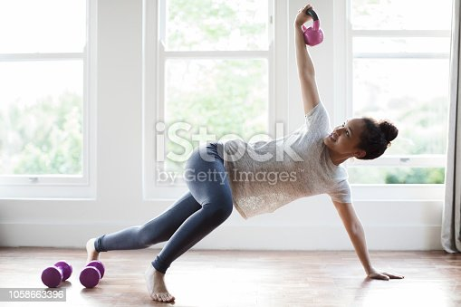 Full length of young woman exercising with kettlebell on hardwood floor. Beautiful female is doing workout in domestic room at home. She is sports clothing.