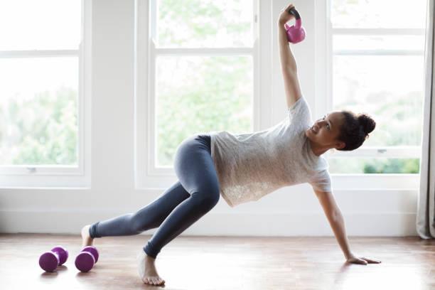 mujer joven haciendo ejercicio con pesas rusas en el país - pesa rusa fotografías e imágenes de stock
