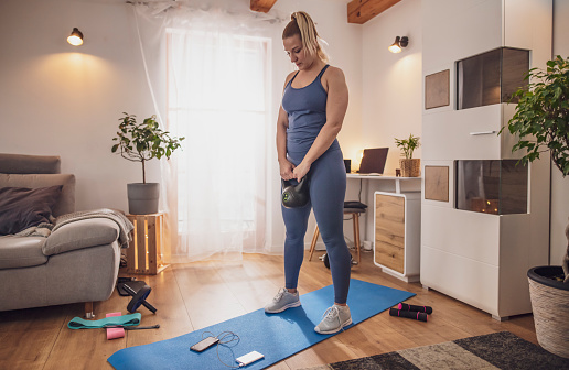 Young Woman Exercising With Kettlebell On Yoga Mat In Living Room Stock Photo - Download Image Now