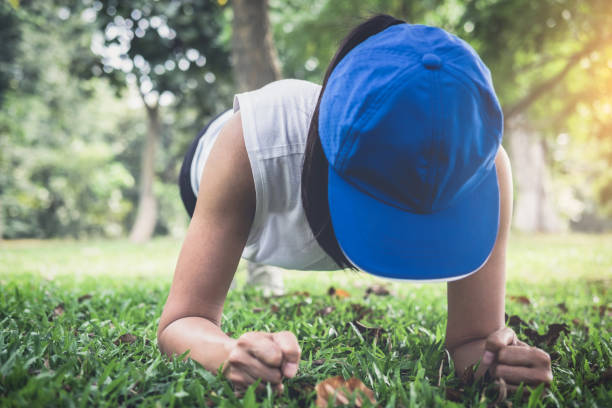 young woman exercising workout fitness doing planking outside on grass  in summer park - peso mosca foto e immagini stock