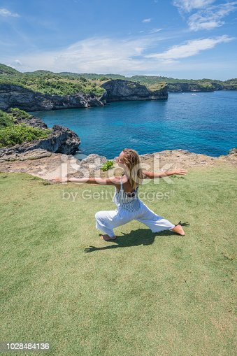 Young woman exercising yoga on rock coastline in Nusa Penida Island near Bali, people travel relaxation concept in nature