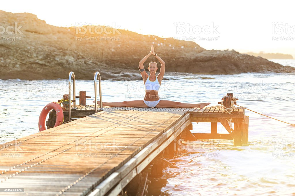 Young woman exercising yoga on the pier stock photo