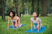 istock Young woman exercising yoga with her daughter 1023553144