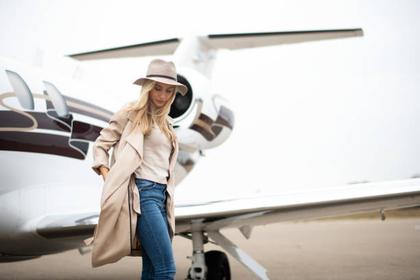 Young woman exiting a private airplane Young successful girl getting out of a private jet parked on a runway. status symbol stock pictures, royalty-free photos & images