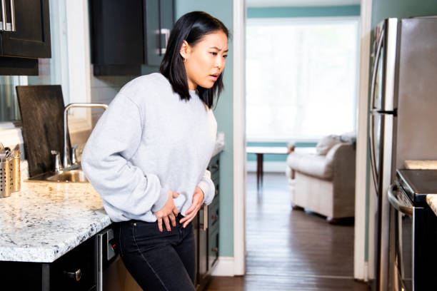 A young woman experiencing pelvic discomfort, she is grimacing in pain. stock photo