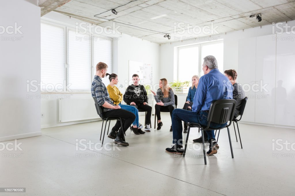 Young woman explaining during mental group therapy Young woman talking with friend during mental health session. Men and women are wearing casuals. They are sitting in university lecture hall. 18-19 Years Stock Photo