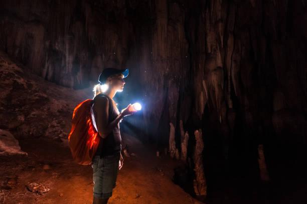 동굴을 탐구 하는 젊은 여자 - 동굴 뉴스 사진 이미지