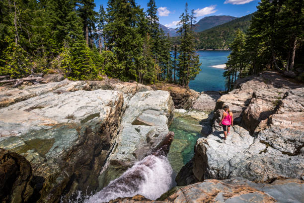 Young woman exploring Strathcona provincial park. Adventurous woman checking out Lower Myra waterfalls. vancouver island stock pictures, royalty-free photos & images