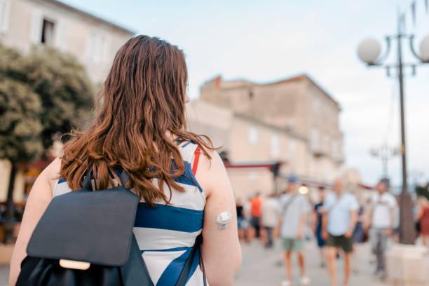 Junge Frau, die Erkundung der Stadt, die einen kontinuierlichen Glukose-Monitor und einen Rucksack tragen – Foto