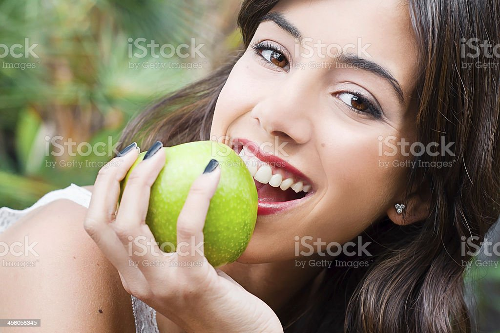 Young woman face eating an apple stock photo