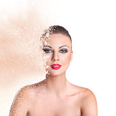 Fashion portrait of young beautiful woman with exploded cloud of face powder combined with pixelated effect