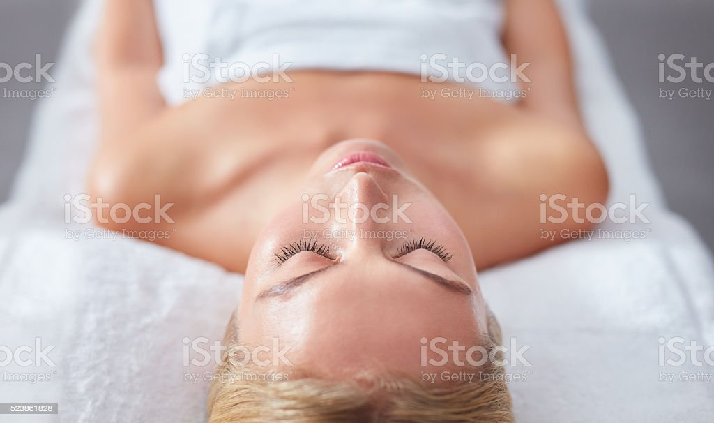 Young woman face relaxing on massage table stock photo
