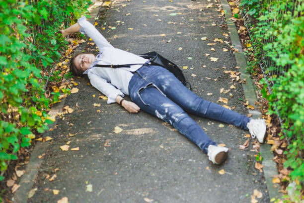 Young woman fainted on the street in the middle of the day stock photo