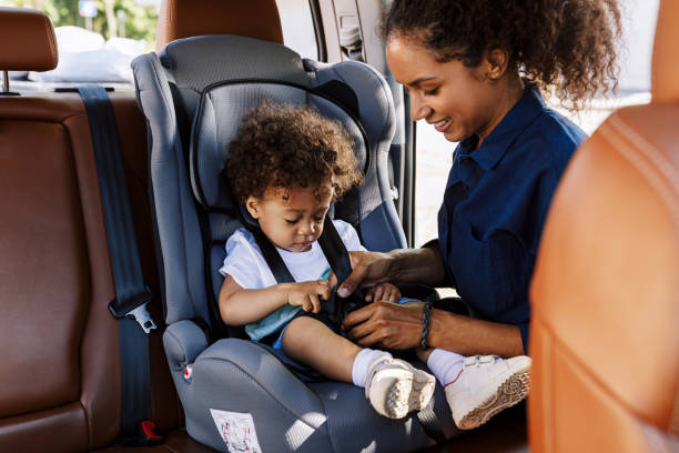 Young woman fastens her son with safety straps in the car stock photo