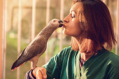 Female veterinarian holding a parrot's food in her mouth while he is trying to take it.