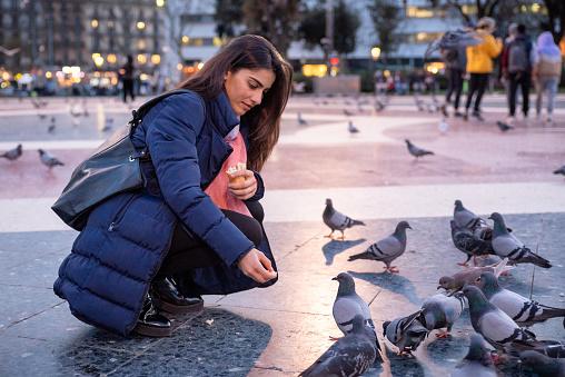 young woman feeding pigeons in plaça catalunya, Barcelona, Spain