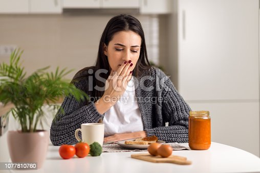 Young woman feeling nausea during breakfast time at home