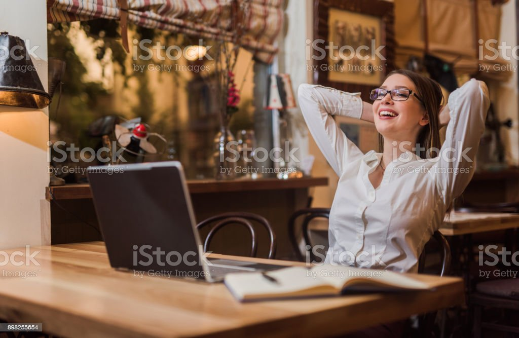 Young woman feeling relieved after late night work is done. stock photo