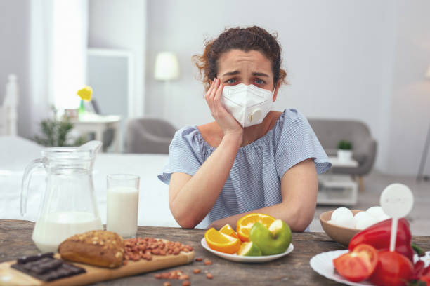 young woman feeling upset about her multiple allergies - food allergies stock photos and pictures