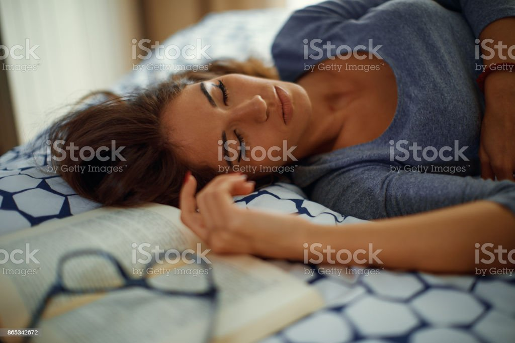Young woman fell asleep while studying on the bed stock photo