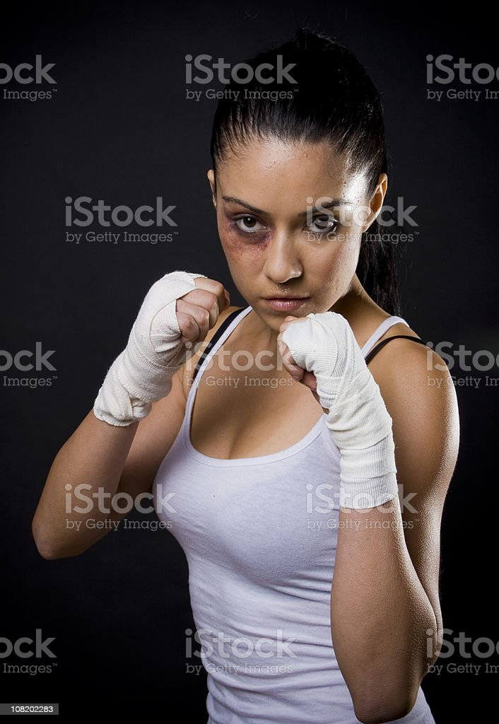 Young Woman Fighter with Black Eye and Taped Hands stock photo
