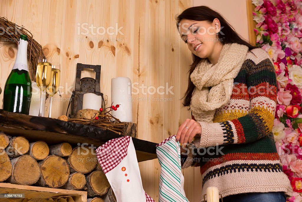 Young woman filling Christmas stockings stock photo
