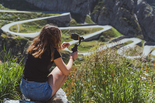 young woman filming the tremola road in san gotthard using a smartphone and a gimbal