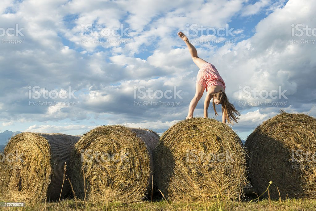 Young Woman Finioshing Cartwheel on Bales of Grass royalty-free stock photo
