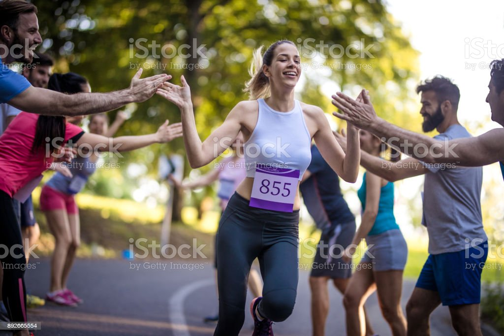 Young woman finishing marathon race and greeting with group of supporters. stock photo