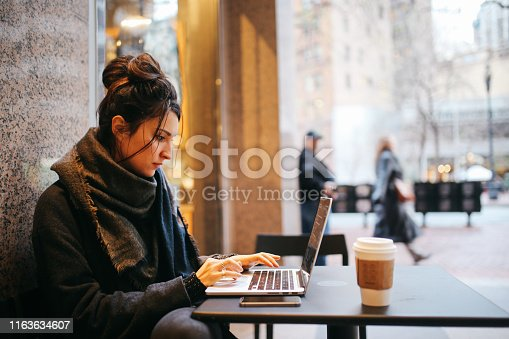 Young woman sitting outdoors in front of the cafe, finishing her work on the laptop, in San Francisco, California.