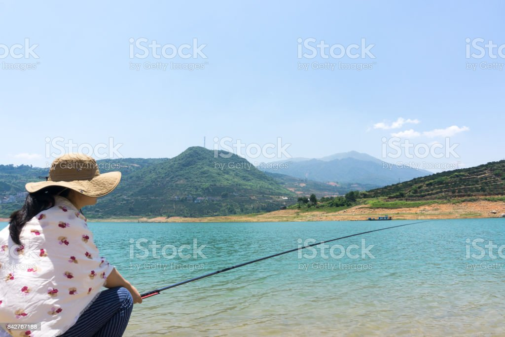 Young woman fishing oudoors stock photo
