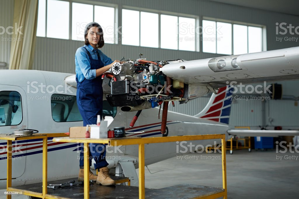 Young Woman Fixing Airplane in Hangar foto stock royalty-free