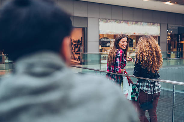 Young woman flirting in the shopping center Girl smiling at stranger in the shopping mall stranger stock pictures, royalty-free photos & images